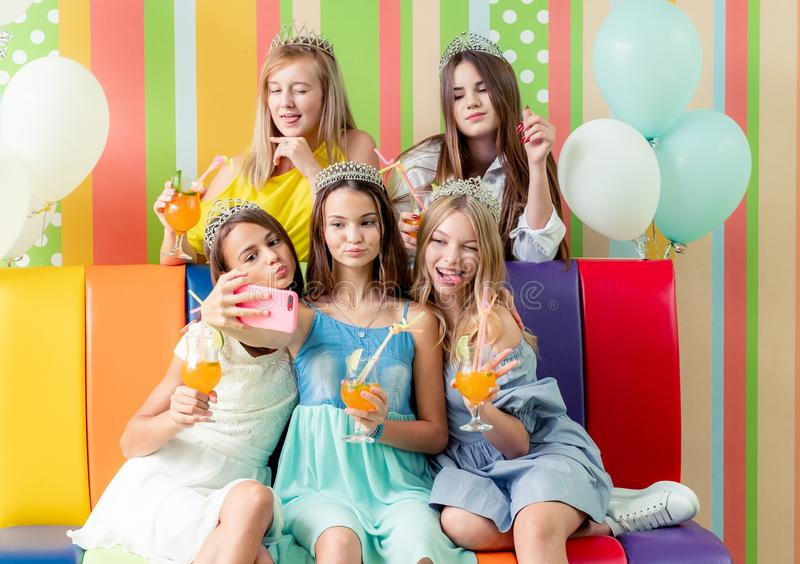 Nätta le tonårs- flickor som tar selfie på födelsedagpartiet royaltyfri foto