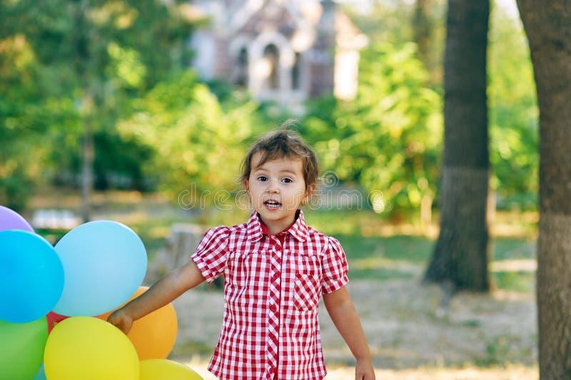 Nätta liten flickahåll i handballonger arkivfoton