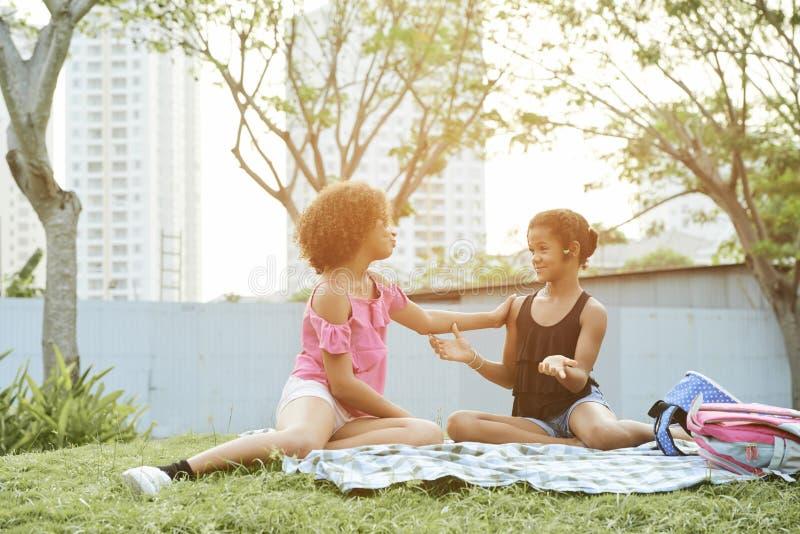Nätta tonåriga flickor som pratar på picknicken royaltyfria bilder