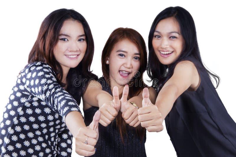 Nätta tonårs- flickor som visar upp tummar arkivbild