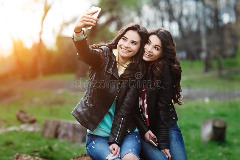 Nätta två och lycklig ung kvinna som använder mobiltelefonen i parkera Bästa vän gör selfie arkivfoto