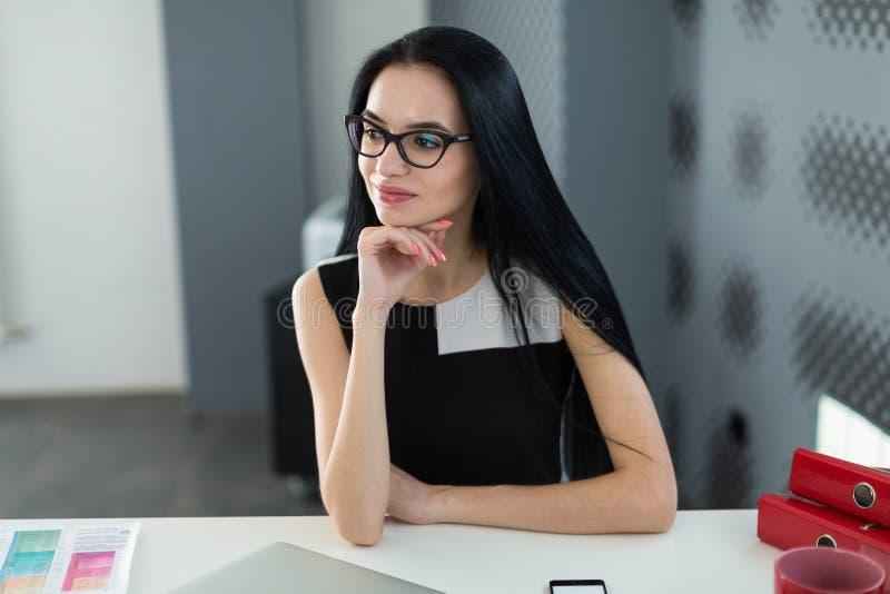 Nätta unga businesslady i svart klänning och exponeringsglas sitter på royaltyfria foton