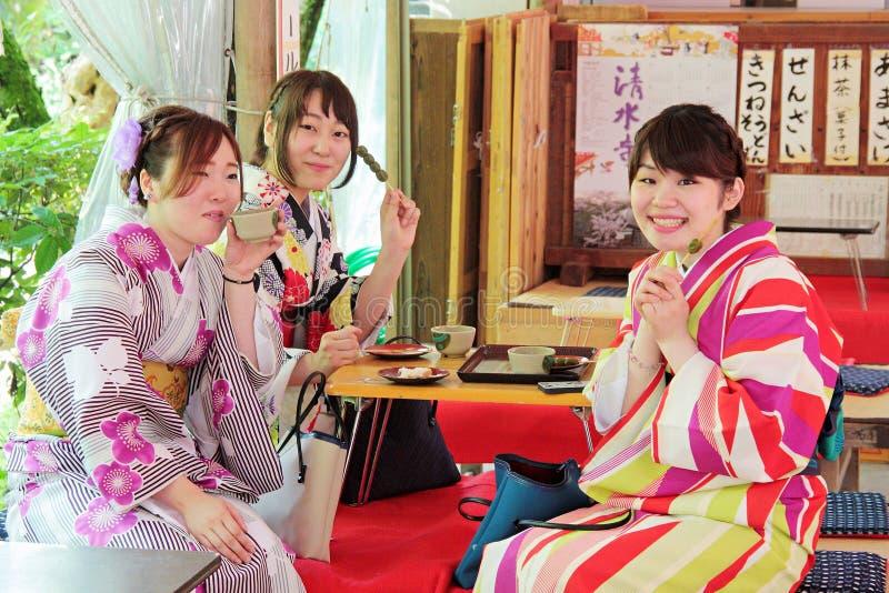 Nätta unga flickor med den färgrika traditionella japanska kimonot som äter ris, klumpa ihop sig steknålar i en japan arkivfoto