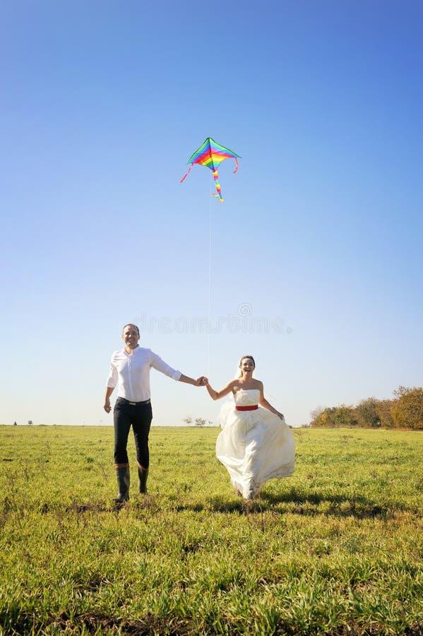 Nätta unga vuxna brölloppar som går på fält med draken royaltyfri fotografi
