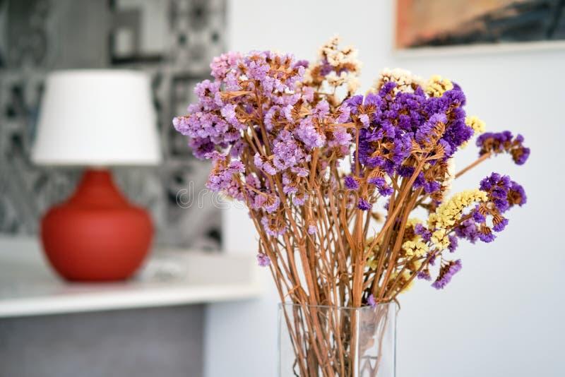 Nätta violetta blommor i exponeringsglasvas hemma royaltyfri fotografi