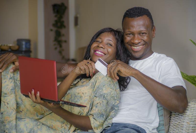 Nätverkande för soffa för soffa för attraktiva svarta afrikansk amerikanpar hemmastadd med bankrörelsen för bärbar datordator dir royaltyfria bilder