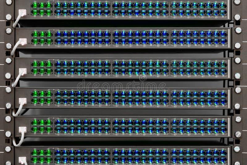 Nätverksrouters av ISP Många trådar förbinder till nätverksmanöverenheterna av kraftiga internetserveror Kuggar med datorutrustni royaltyfri foto
