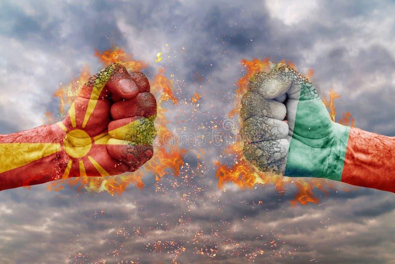 Näve två med flaggan av Makedonien och Bulgarien vände mot på de arkivbilder