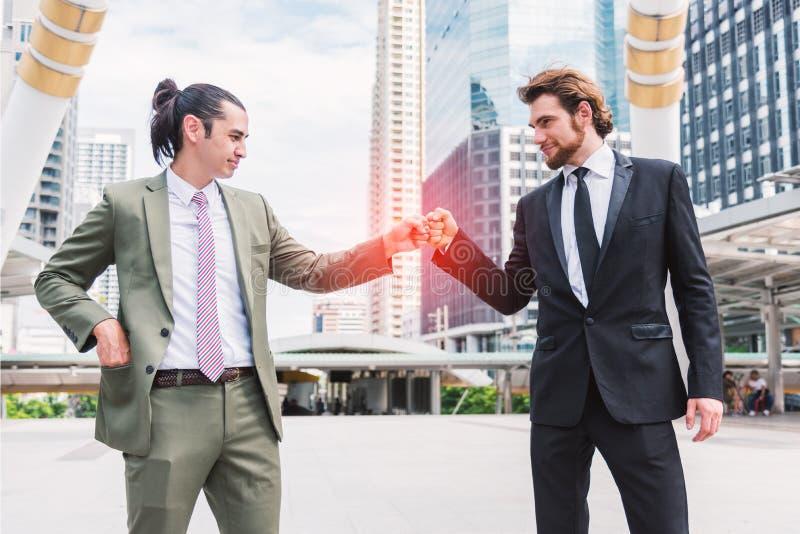 Nävebula eller knogebula mellan överenskommelse för två affärsmän på utomhus- i staden, affärssamarbetet och deltagandebegreppet arkivbilder