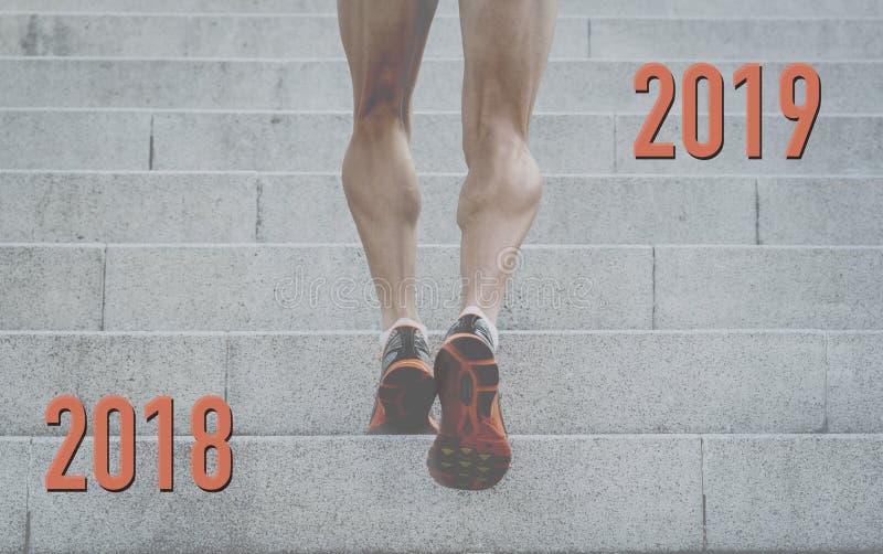 Nå dina mål i 2019 begreppsmässiga bild av starka ben av den unga mannen som upp kör stadstrappa arkivbilder