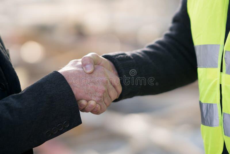 Nå en överenskommelse på konstruktionsplats fotografering för bildbyråer