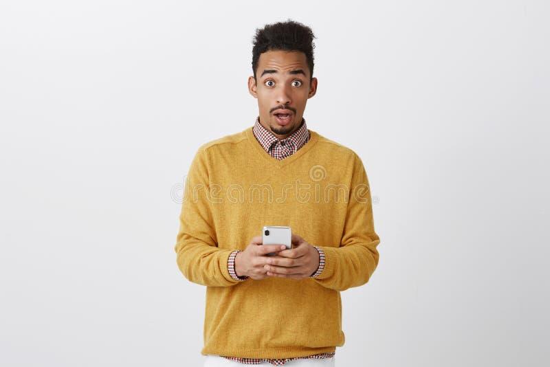 Någon försökte att hacka hans telefon Chockad stilig pojkvän med den afro frisyren i moderiktig kläder som rymmer smartphonen arkivfoton