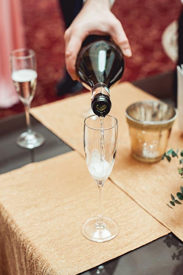Någon hällande vin in i exponeringsglas i detalj royaltyfri foto