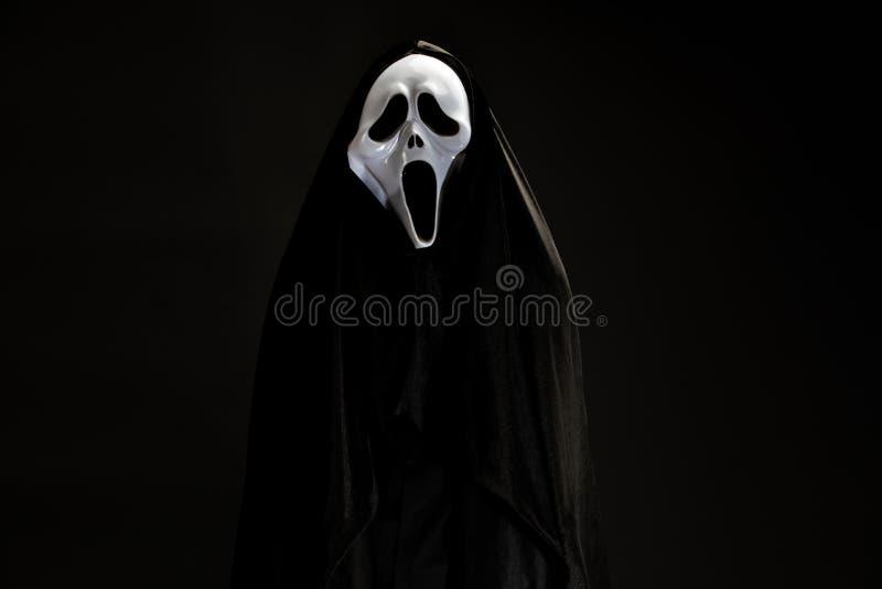 Någon i svart räkning med den vita spökemaskeringen som är cosplay till jäkelac royaltyfri foto