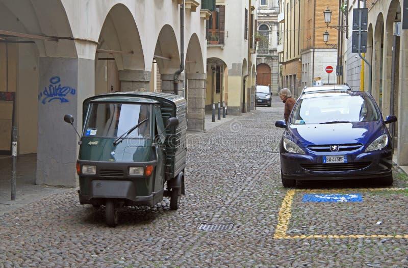 Någon kör en motorisk trehjuling på den smala gatan i Padua arkivbild