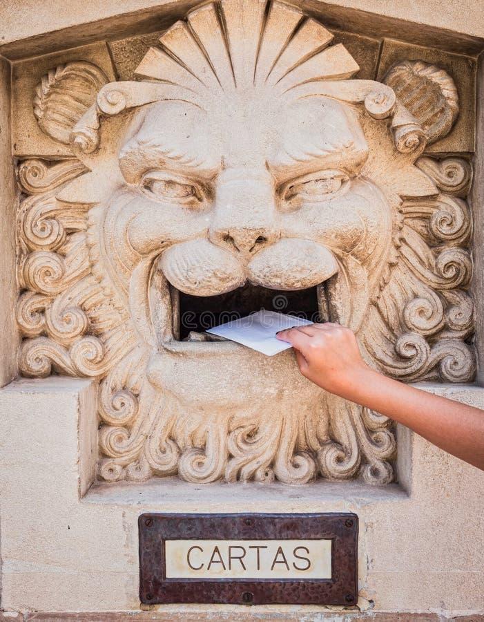 Någon som kastar en bokstav i en gammal brevlåda arkivfoton