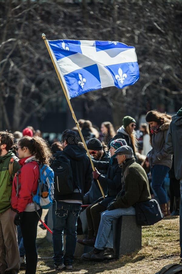 Någon som rymmer den Quebec landskapflaggan i folkmassan royaltyfri bild