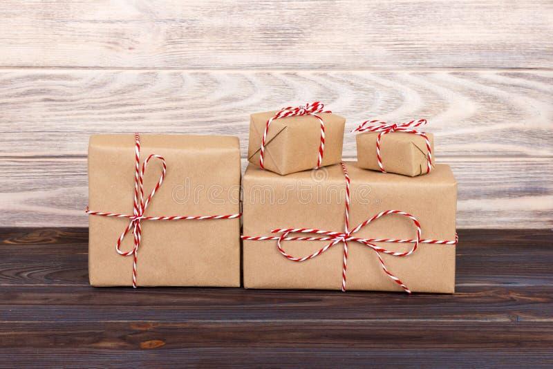 Något papper slår in julgåvaaskar som slås in med papper kraft, och bundet med den röda vita bagaren tvinna i en mörk trätabell c royaltyfria foton