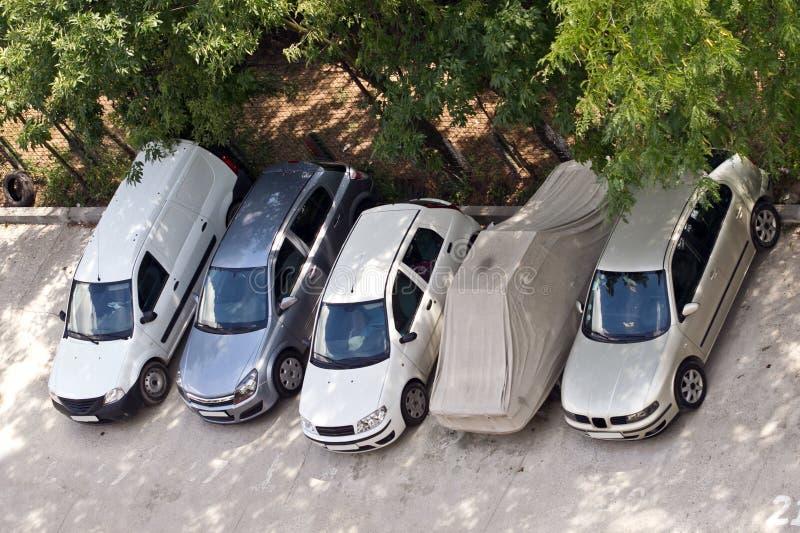 Några bilar som parkeras i en framdel av kvarteret royaltyfria bilder