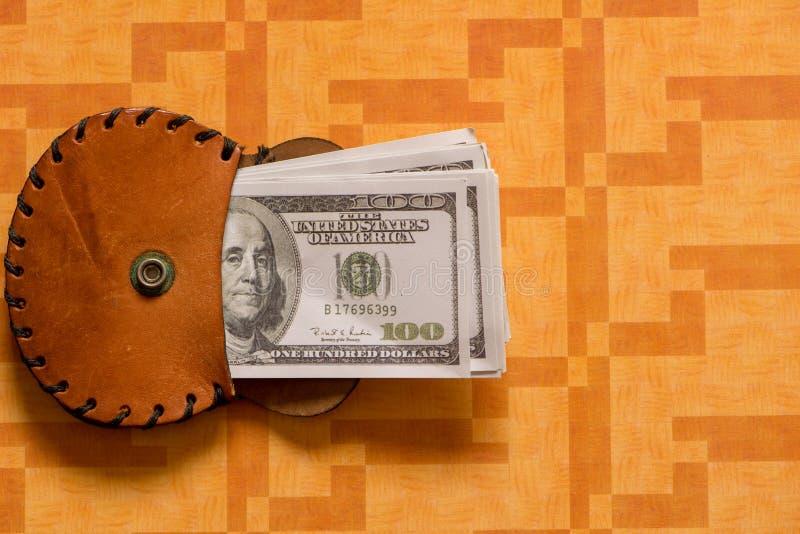 Några dollarräkningar i en brun plånbok royaltyfri foto
