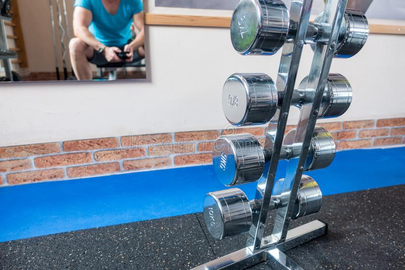 Några försilvrar hantlar är i förgrunden och en spegel med spegelbilden av hängningar för en idrottsman nen på väggen royaltyfri fotografi