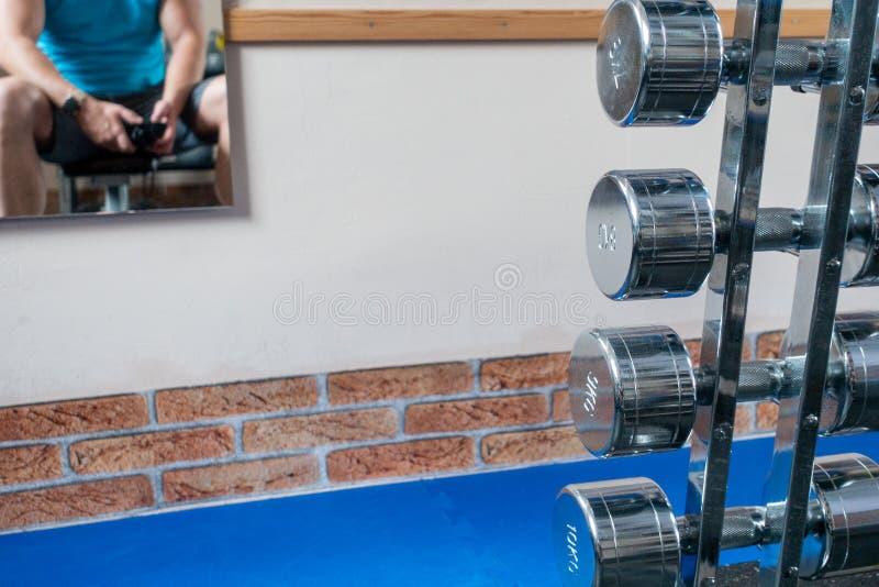 Några försilvrar hantlar är i förgrunden och en spegel med spegelbilden av hängningar för en idrottsman nen på väggen royaltyfria foton