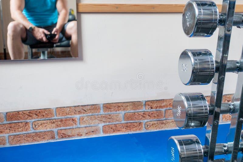Några försilvrar hantlar är i förgrunden och en spegel med spegelbilden av hängningar för en idrottsman nen på väggen royaltyfri bild