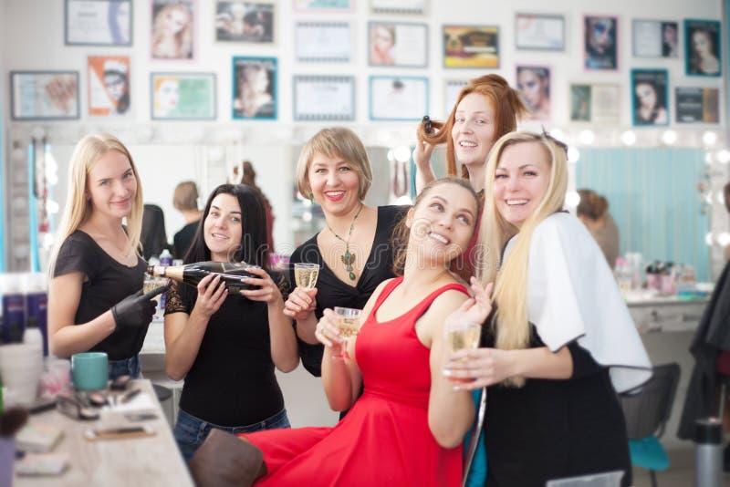 Några gladlynta unga kvinnor som dricker champagne på en skönhetsalong Möhippa eller flickvänner i en skönhetsalong arkivbilder