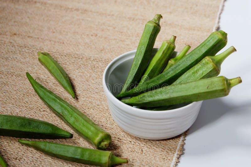 Några gröna okra eller okro eller sockerkaksbit i form av ett finger arkivbilder