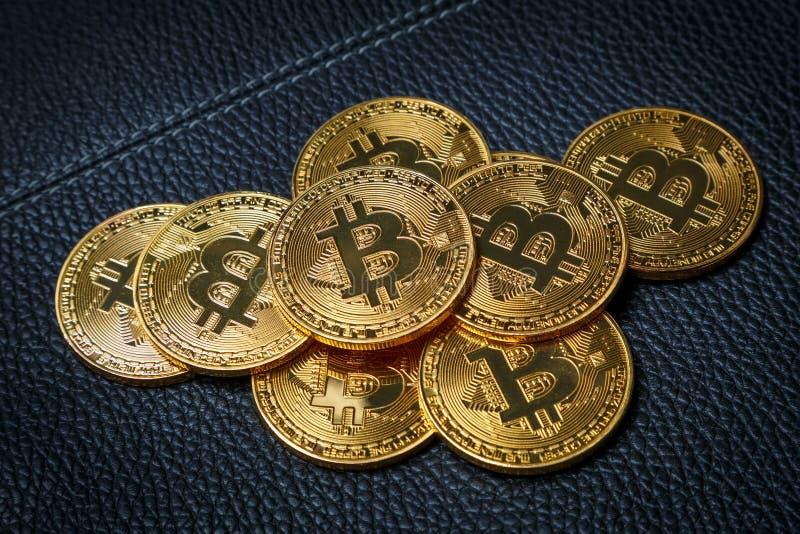 Några guld- mynt med ett bitcointecken på en svart läderbakgrund royaltyfri fotografi