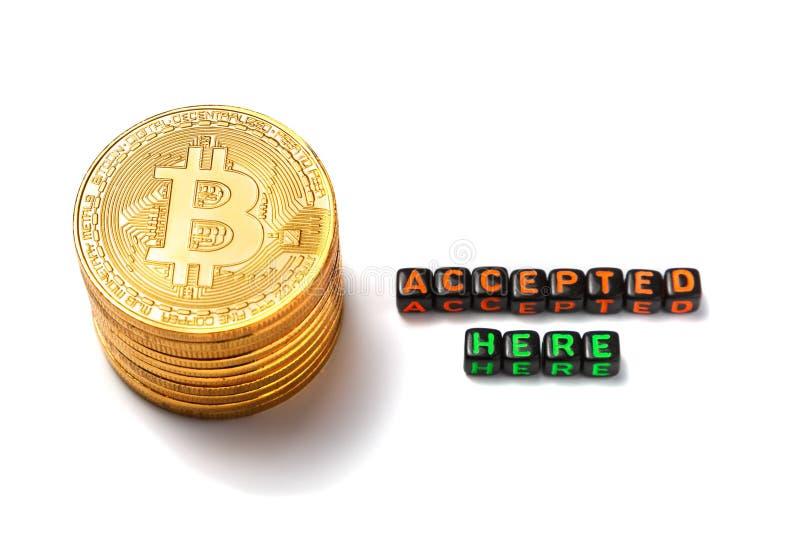 Några guld- mynt med tecknet av bitcoin och inskrift`en accepterade här ` på en vit bakgrund arkivbilder