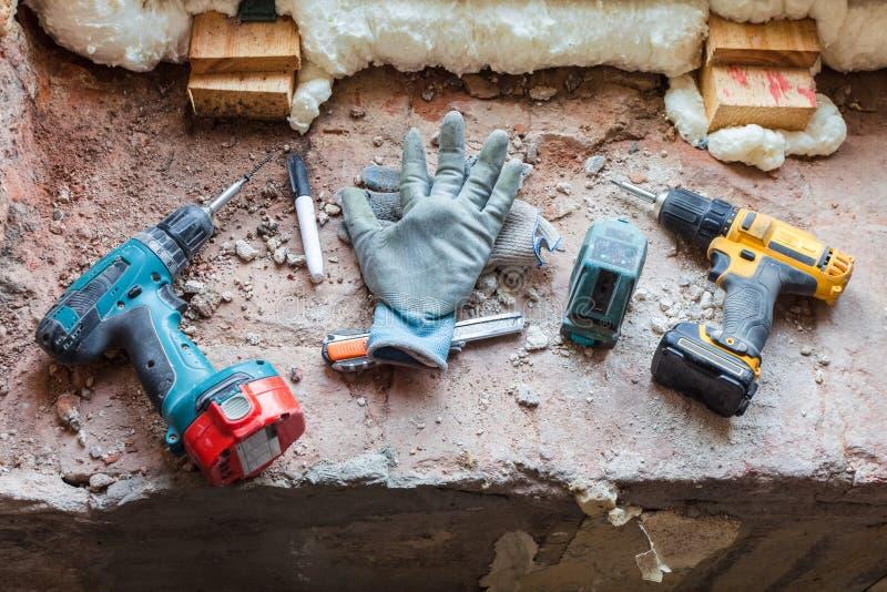 Några hjälpmedel - drillborren, skruvmejsel och att montera kniven och att montera elektroniska handskar för nivå- och arbetar` s royaltyfria foton