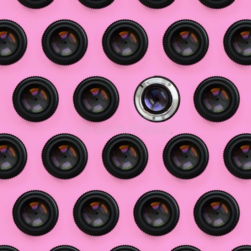 Några kameralinser med en stängd öppningslögn på texturbakgrund av pastellfärgat rosa färgpapper för mode i minsta begrepp royaltyfri fotografi