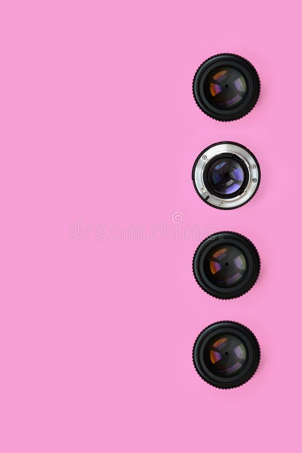 Några kameralinser med en stängd öppningslögn på texturbakgrund av pastellfärgat rosa färgpapper för mode i minsta begrepp arkivfoto