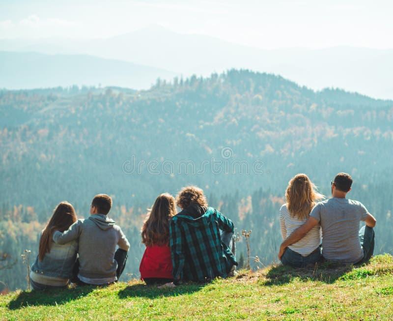 Några kopplar ihop handelsresandepojkar och flickor som sitter på för sinnesrörelselivsstil för klippa som lyckligt resa för fami royaltyfri fotografi
