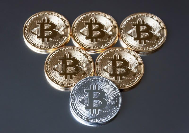 Några ligger blir guld- och silvermyntbitcoin eller på kanten på en mörk bakgrund Begreppet av crypto valuta arkivbild