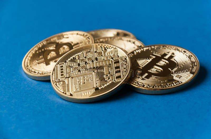 Några ligger guld- och silvermyntbitcoin på en blå backgroundConcept av crypto valuta arkivfoton