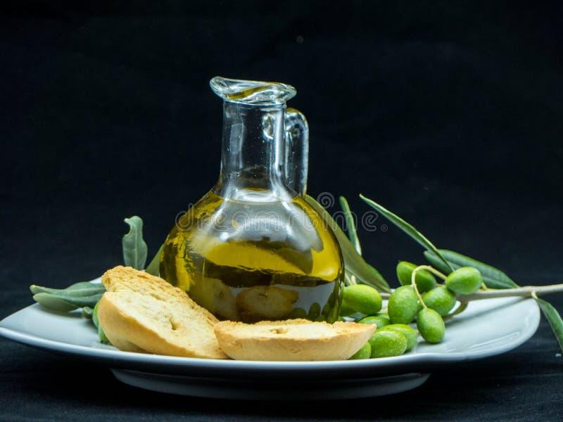 Några oliv och en krus mycket av olja och en filial av olivträdet på arkivbilder
