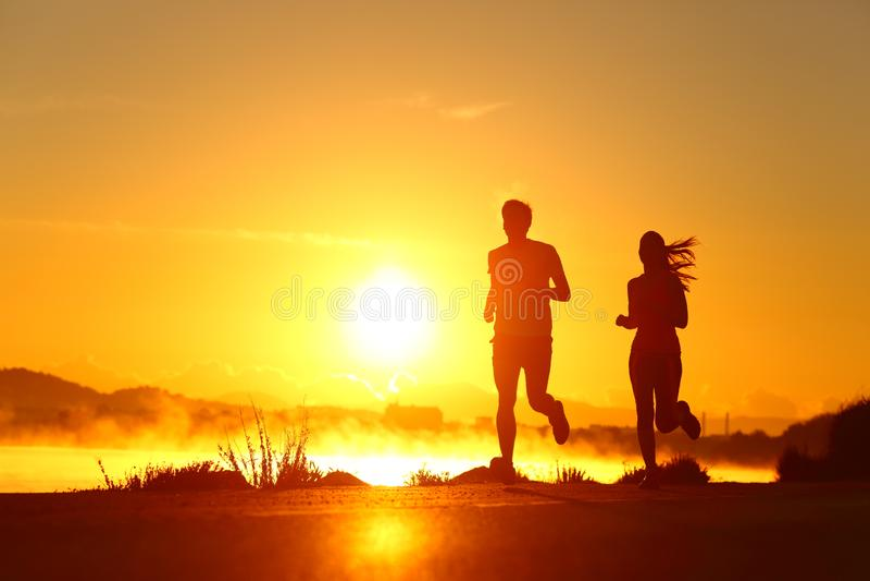 Några shilouette som springer vid soluppgång på stranden arkivbild