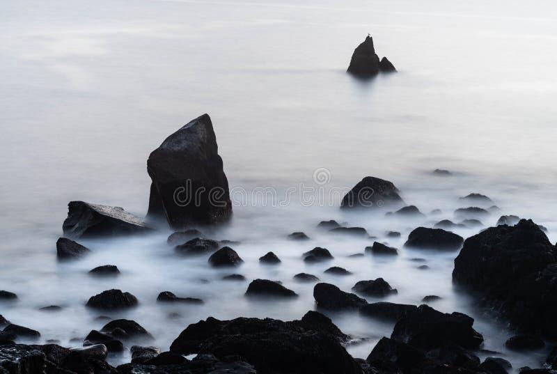 Några stenar och ett lugna hav royaltyfri fotografi