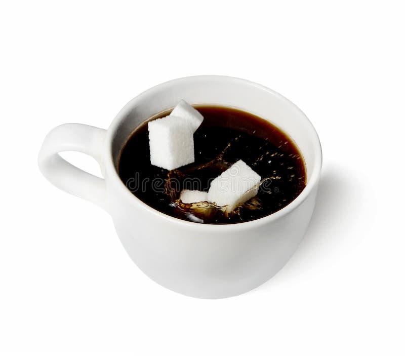 Några stycken av socker som faller in i en vit kopp kaffe Vit isolerad bakgrund färgstänk fotografering för bildbyråer