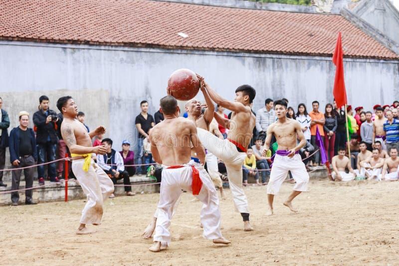 Några unga män spelar med den wood bollen i mån- nytt år för festival på Hanoi, Vietnam på Januari 27, 2016 royaltyfri bild