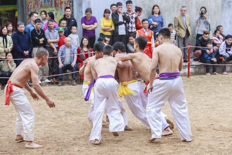 Några unga män spelar med den wood bollen i mån- nytt år för festival på Hanoi, Vietnam på Januari 27, 2016 royaltyfria foton