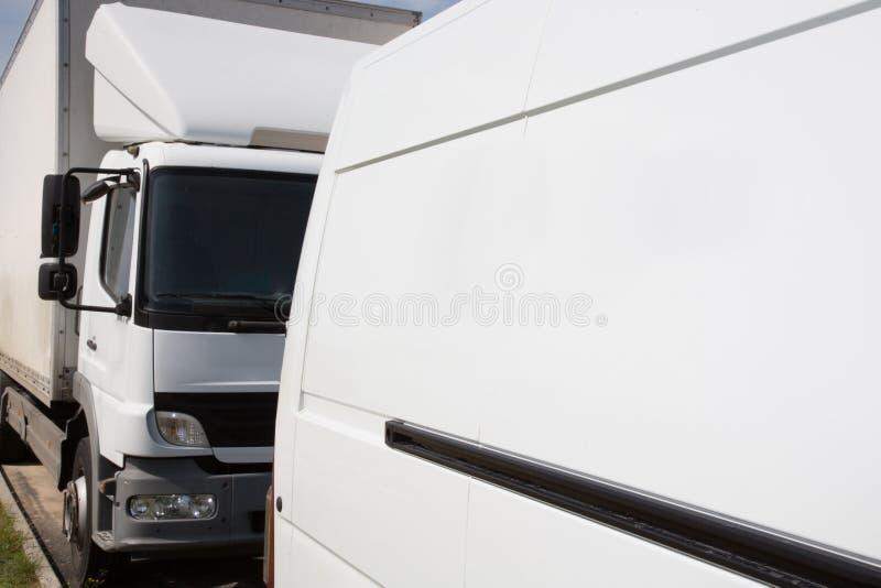 Några vita lastbilar skåpbil leverans i lager parkerar royaltyfri fotografi
