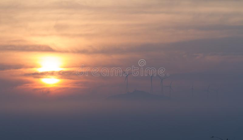 Névoa e moinhos de vento do nascer do sol durante invernos indianos foto de stock