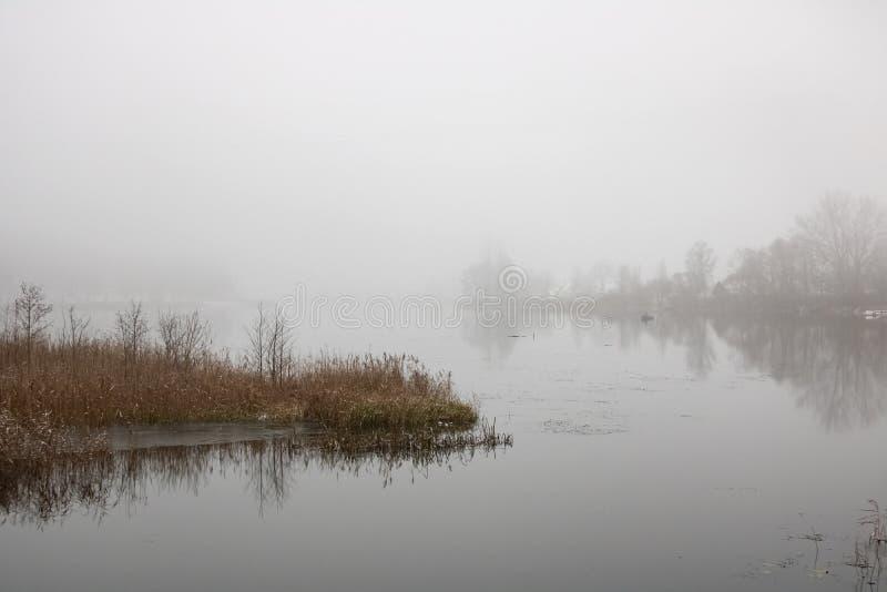 Névoa grossa sobre o rio e um barco foto de stock