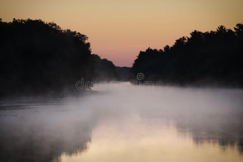 Névoa macia que paira sobre o enrolamento do rio através da região selvagem, céu fotos de stock royalty free