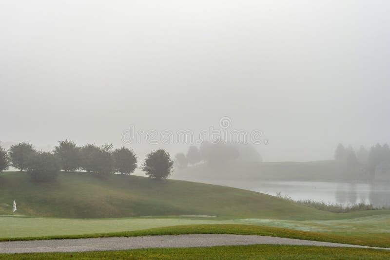 Névoa pesada sobre o campo de golfe na manhã adiantada da mola fotografia de stock