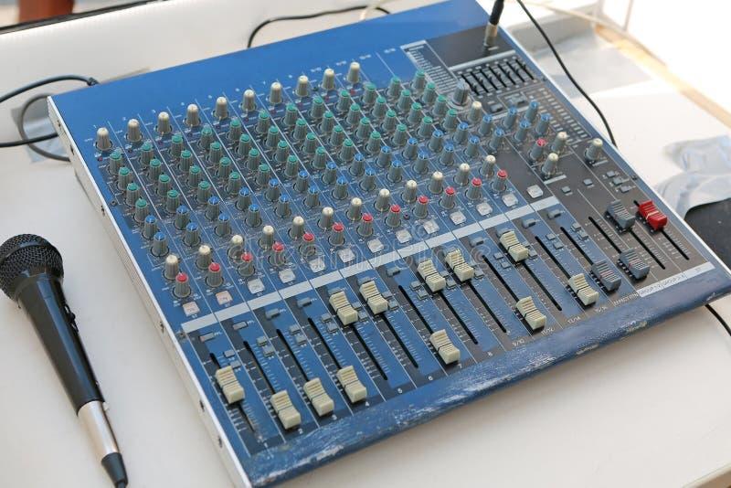 Níveis sadios em um misturador audio profissional com microfone, painel de controle da música imagem de stock royalty free