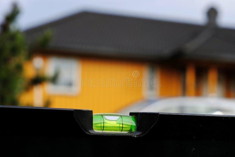 Nível de espírito preto em um fundo de uma casa amarela com um telhado preto foto de stock royalty free